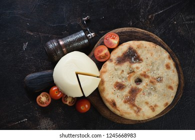 Ossetian pie with meat and suluguni cheese on a dark brown stone background, flatlay, horizontal shot