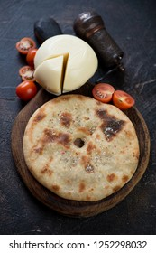 Ossetian pie with meat and suluguni cheese, vertical shot on a dark brown stone background