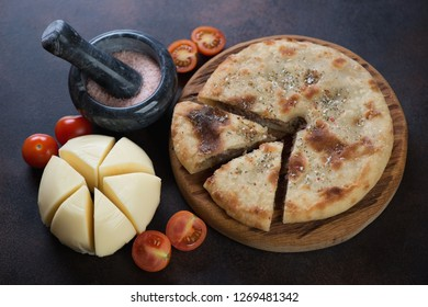 Ossetian pie with meat, suluguni cheese and cherry tomatoes. Studio shot on a dark brown metal background