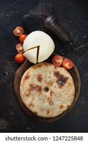 Ossetian pie, suluguni cheese and cherry tomatoes over dark brown stone background, vertical shot, view from above