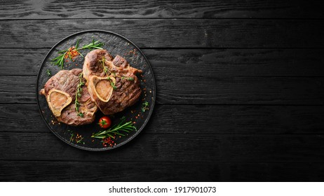 Osso buco cooked Veal shank with spices and rosemary. Barbecue meat. Top view. Flat lay top view on black stone cutting table.