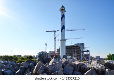 Ostend, Belgium - 22 June 2019: Lange Nelle lighthouse with new residential construction Oosteroever district in background and typical cobblestones in the foreground