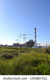 Ostend, Belgium - 22 June 2019: construction new city district Oosteroever in Ostend with famous Lange Nelle lighthouse and green nature dunes landscape in foreground