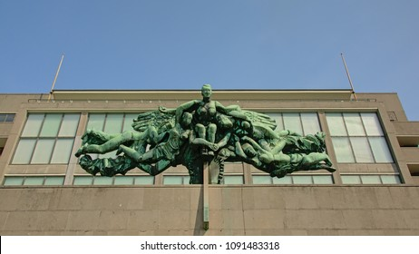 OSTEND, BELGIUM, APRIL 21, 2018, Brass sculpture `De communicatiemedia` by Jozef Cantre on the old `Grote Post` postal building in Ostend, 21 April 2018
