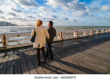 OSTEND, BELGIUM - DECEMBER 7, 2007: Couple on vacation with sunny weather looking at the skyline of the city seen from the pier with a harsh North Sea storm.