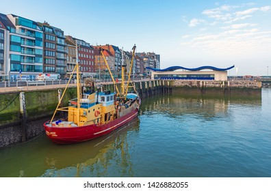 OSTEND, BELGIUM - FEBRUARY 5, 2019: Fishing boat in the harbor of Oostende city by the waterfront promenade with the modern fish market in the background.