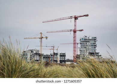 OSTEND, BELGIUM - JANUARY 1, 2019: new apartment buildings at Oosteroever with construction cranes and dunes in foreground