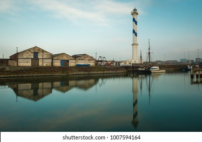 OSTEND, BELGIUM - JANUARY 12, 2018: The lighthouse of Oostende reflecting in a commercial dock of the harbor with a few warehouses.