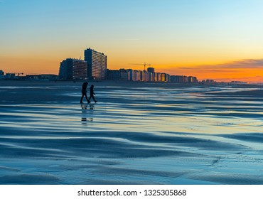OSTEND, BELGIUM - JANUARY 30, 2019: Reflection of two silhouettes of people walking on the North Sea beach of Ostend City with its urban cityscape in the background at sunset, West Flanders, Belgium.