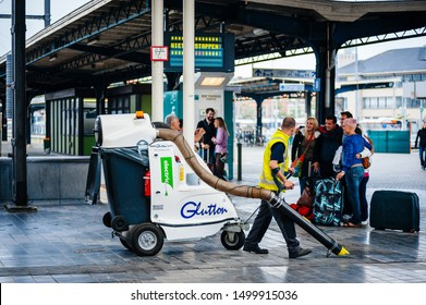 Ostend, Belgium - Jul 16, 2011: Worker using electric vacuum machine Glutton looking at travelers taking a group photo in Ostend Centraal Train station