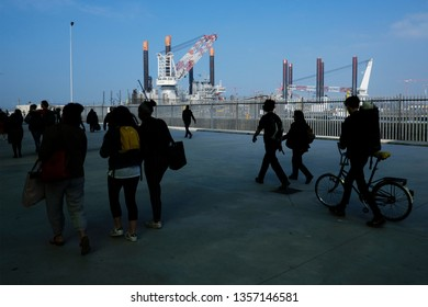 Ostend, Belgium Mar. 30, 2019. People walk in front of an oil extraction platform in port of Ostend.