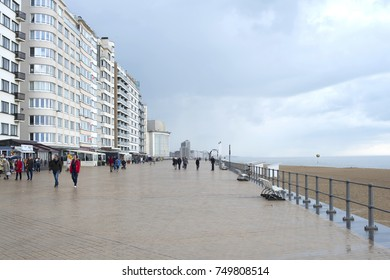 Ostend, Belgium, May 11, 2017 -- Oceanfront promenade with a cloudy sky after the Rain in Ostend (Oostend), Belgium, with people wearing coats enjoying a beachfront walk.