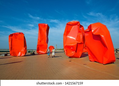 Ostend, Belgium-07 24 2014:People walking on the promenade pier, admiring the Conceptual work of art named Rock Strangers by Belgian conceptual artist Arne Quinze at seaside resort Ostend.
