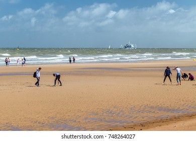 OSTENDE, BELGIUM - JUNE 9, 2017: The teenagers walking on the beach in Ostende, Belgium. Summer day, the sun, at the sea a storm, youth plays active games