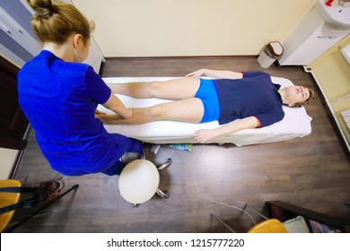 Osteopath in blue does massage of legs for teenager in clinic, top view
