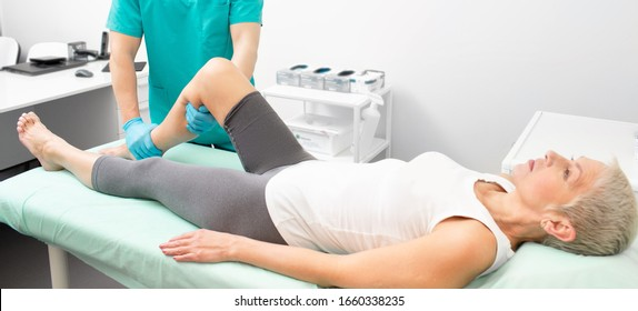 Osteopath doing a diagnosis of a woman's leg. Woman may have a broken leg