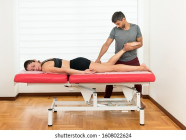 Osteopath doing a myofascial hamstring manipulation on a young woman patient bending her leg at the knee as she lies on an examination couch in an alternative medicine and healthcare concept