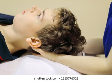 Osteopath hands do massage of head for teenager in modern clinic, focus on boy