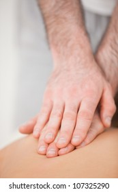 Osteopath massaging his patient while pressing his back in a room
