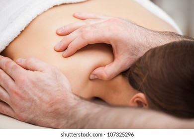 Osteopath massaging his patient while pressing his tumb in a room