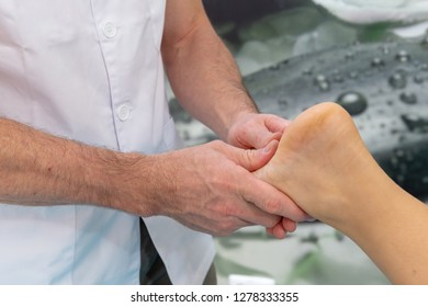 Osteopath therapist makes manipulation and massage to foot the patient.