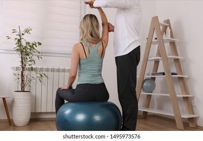 Osteopathy / Kinesiology treatment exercise ball. Sport Injury rehabilitation of athlete female patient.