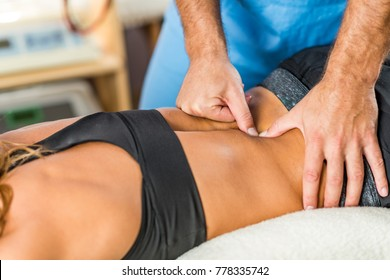 Osteopathy. Therapist applying strong pressure onto lower back muscles