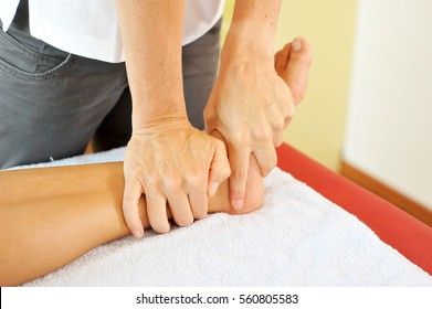 Osteopathy therapist is diagnosing and treating the ankle of a young female caucasian patient