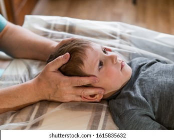 Osteopathy Treatment. Elementary age boy's forehead being manipulated by real osteopathic physician