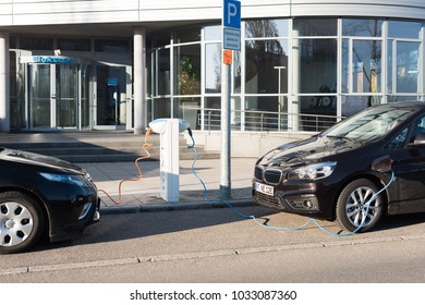 Ostfildern, Germany - February 24, 2018: A BMW i and an Opel Ampera electric cars are being charged at a power charging station in Ostfildern, Germany.