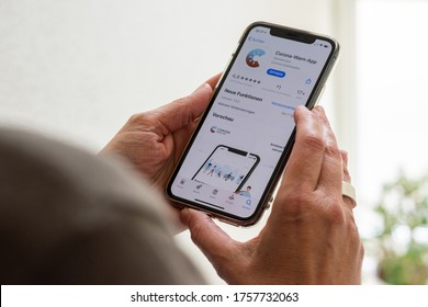 Ostfildern, Germany - June 16, 2020: A middle aged woman is about to download the new smartphone app to combat the corona pandemic on her Apple iPhone 11 Pro. The app is comissioned from the German