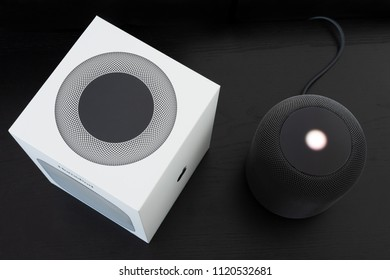 Ostfildern, Germany - June 25, 2018: Unboxing an Apple HomePod speaker: The speaker is standing next to its box, ready to receive voice commands.