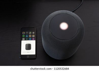 Ostfildern, Germany - June 25, 2018: Installing an Apple HomePod speaker: The speaker is being configured using the settings of the iPhone being placed next to it.