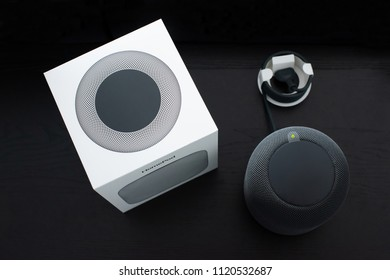 Ostfildern, Germany - June 25, 2018: Unboxing an Apple HomePod speaker: The speaker is moved out of its box with the power cable still assembled in its cardbox housing.