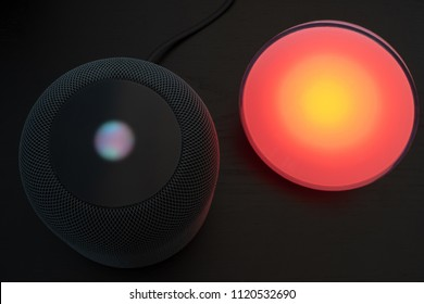 Ostfildern, Germany - June 25, 2018: Using an Apple HomePod speaker to control a Philips Hue smart light - concept for Smart Home technology