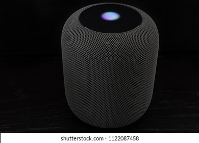 Ostfildern, Germany - June 26, 2018: Using an Apple HomePod speaker - the smart speaker is reacting to voice input and signalling its attention by the changing lights