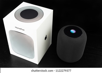 Ostfildern, Germany - June 26, 2018: Unboxing an Apple HomePod speaker: The speaker is standing next to its iconic box, ready to receive voice commands.