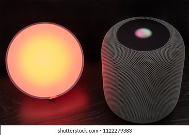 Ostfildern, Germany - June 26, 2018: Using an Apple HomePod speaker to control a Philips Hue smart light - concept for Smart Home technology