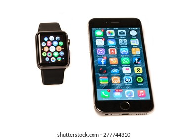 OSTFILDERN, GERMANY - MAY 13, 2015: The new Apple Watch, a black 42mm Apple Watch Sport displaying the apps screen next to the iPhone 6 displaying the home screen. The Apple Watch is the latest device