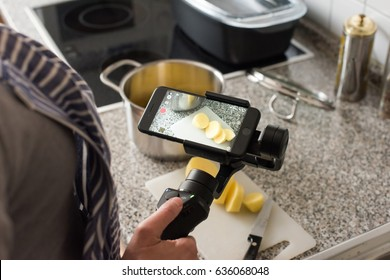 Ostfildern, Germany - May 7, 2017: A female blogger is producing a video while cooking using the DJI Osmo Mobile steadycam gimbal and an Apple iPhone 7.