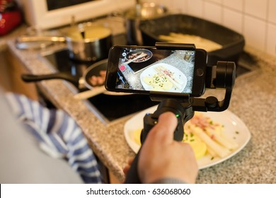 Ostfildern, Germany - May 7, 2017: A female blogger is producing a video while preparing the final dish consisting of asparagus with potatoes, ham and hollandaise sauce using the DJI Osmo Mobile