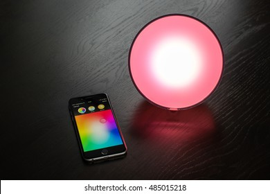 Ostfildern, Germany - September 4, 2016: The Philips Hue app on an Apple iPhone is used to control a Philips Hue smart home light on a dark wooden table or shelf. Using the Apple HomeKit technology