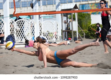 OSTIA, ITALY. May 12, 2015: Rushing woman try to receive the ball during a beach volley match between friends on the sand at the sea in Ostia, a town near Rome in Italy. Summer sports.