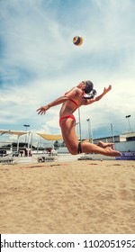 OSTIA, ITALY. May 27, 2015: Woman hit the ball jumping during a beachvolley match between friends on the sand at the sea in Ostia, a town near Rome in Italy. Summer sports and recreation activity.