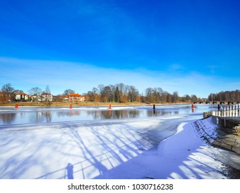 Ostra Bron bridge is located in central part, view the river snow with the branches of the tree where the leaves fall with blue sky background in winter season at Karlstad, Sweden