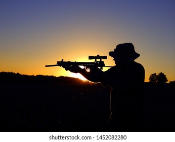 Ostrava, czech republic August, 5 2017. Silhouette of man with crossbow in the field with gamekeeper´s  hideout in the background.