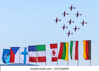 OSTRAVA, CZECH REPUBLIC - SEPTEMBER 22, 2019: NATO Days. Swiss Air Force PC-7 team performs a flight display. Colorful flags of NATO countries waving in the wind.