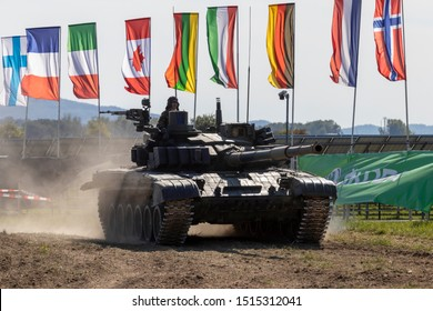 OSTRAVA, CZECH REPUBLIC - SEPTEMBER 22, 2019: NATO Days. Old Russian T-72 tank of the Czech armed forces performs a demonstration. Flags of NATO countries waving in the wind.