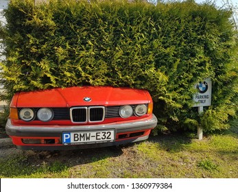 Ostritz, Saxony/Germany - April 6th 2019. Special private parking lot reserved for BMW cars only. Funny because of old BMW E32 stuck in a hedge