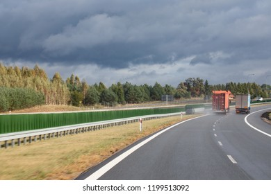 Ostroda / Poland - 10.03.2018: New build highway S7, trucks overtaking, passing each other, stormy sky.
